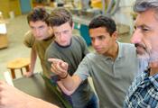 Links drei junge Männer, die zuhören, rechts ein älterer Mann, der etwas erklärt.
