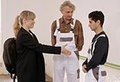 Eine Frau und ein junger Mann stehen einander gegenüber. Ein älterer Mann schaut zu.