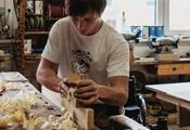 Junger Tischler bei der Arbeit, dahinter ist ein Rollstuhl zu erkennen