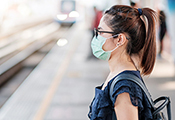 Junge Frau mit Mund-Nasen-Maske an einer S-Bahn-Haltestelle