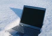 Das Bild zeigt einen Laptop, der im tiefen Schnee liegt