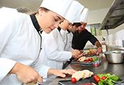 Auszubildende für den Beruf des Kochs bereiten Speisen zu
