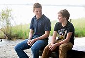 Student und Jugendlicher, auf einem Steg sitzend