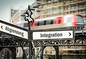 """Wegweiser an einer Straßenkreuzung. Einer zeigt in Richtung """"Ausgrenzung"""" der andere in Richtung """"Integration""""."""
