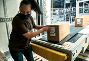Junge Frau beim Verladen von Postpaketen